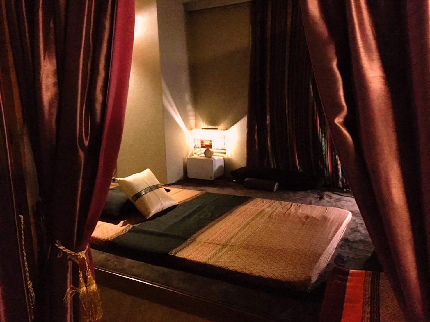 オイルマッサージ、ストレッチ、タイ古式マッサージの施術の様子。室内の風景